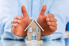 Male hands saving Miniature House Royalty Free Stock Images