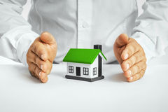 Male hands saving small house Royalty Free Stock Photos