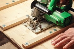 Male hands sawing boards with a circular saw royalty free stock images