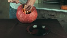 Male hands scooping out seeds and contents of pumpkin. Halloween theme, jack lantern. Close up shot stock footage