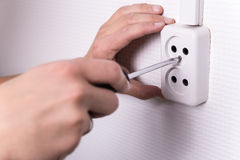 Male hands with screwdriver installing electrical socket on wall. Close up of male hands with screwdriver installing electrical socket on wall royalty free stock image