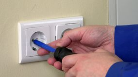 Male hands with screwdriver repairing electrical outlet stock footage