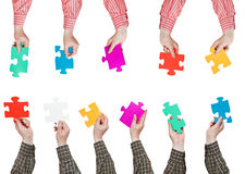 Male hands in shirt sleeves with puzzle pieces. Male hands in shirt sleeves with different puzzle pieces isolated on white background Stock Photography