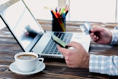 Male Hands Shopping On Internet With Credit Card. Male Hands Shopping On Laptop With Credit Card And Smartphone Royalty Free Stock Photos