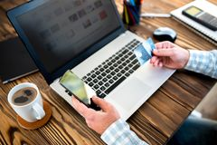 Male Hands Shopping On Laptop With Credit Card. On Rustic Wooden Table In Office Stock Photo