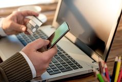 Male Hands Shopping Online With Credit Card. On Rustic Wooden Table In Office Royalty Free Stock Images