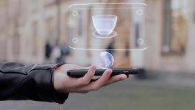 Male hands show on smartphone conceptual HUD hologram cup of coffee. Man with the future technology mobile holographic screen on blurred background of the