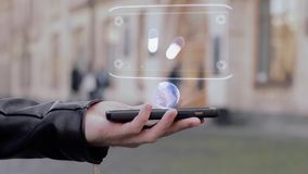 Male hands show on smartphone conceptual HUD hologram pills. Man with the future technology mobile holographic screen on blurred background of the university