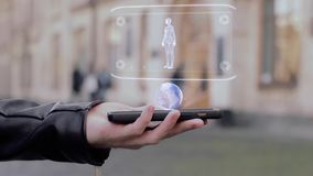 Male hands show on smartphone conceptual HUD hologram woman body. Man with the future technology mobile holographic screen on blurred background of the