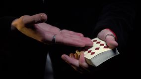 Male hands showing focus with playing cards. Male magician in black jacket shows focus with cards stock footage