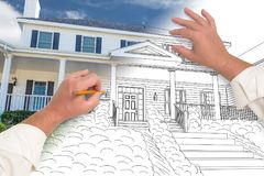 Male Hands Sketching with Pencil the Outline of a House. With Photo Showing Through stock photography