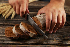 Male hands slicing bread on brown wooden background. Royalty Free Stock Photography