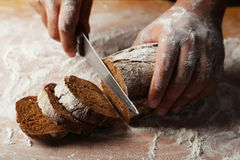 Male hands slicing fresh bread. Royalty Free Stock Images