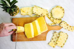 Male hands slicing pineapple fruit on a board Royalty Free Stock Images