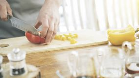 Male hands slicing red paprika on a wooden cutting board stock image