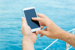 Male hands with smartphone. On sailing, with sea in the background royalty free stock photo