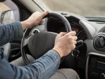 Male hands on steering wheel, inside cab, close up. Man driving a car. stock images