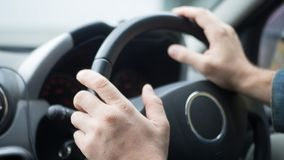 Male hands on steering wheel inside car, selected focus stock photography