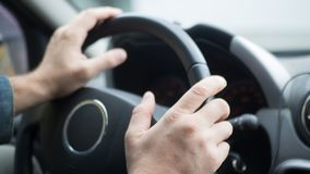 Male hands on steering wheel inside car, selected focus stock images