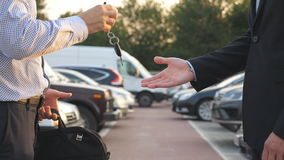 Male hands in suit giving keys of car to his friend. Arm of businessman passes car key. Handshake between two business. Men outdoor. Close up Slow motion stock video footage