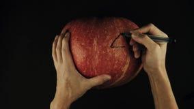 Male hands swipes scary face jack o lantern off a pumpkin using sponge black surface POV stock video footage