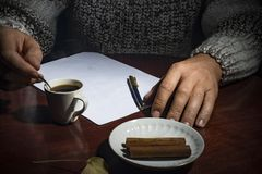 Men`s hands lie on the table, with a cup of coffee and a white sheet of paper, on a dark background Stock Photos