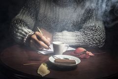 Men`s hands lie on the table, with a cup of coffee and a white sheet of paper, on a dark background Royalty Free Stock Photos