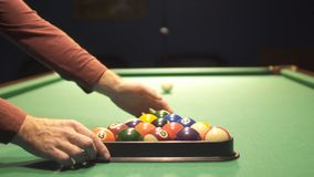 Man takes away plastic triangle from billiard balls. Male hands take away a plastic triangle. The billiard balls is placed for a new game stock video footage
