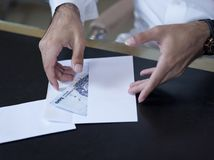 Male Hands taking money out of an envelope Royalty Free Stock Images