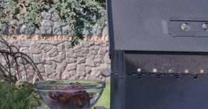 Male hands taking off cooked meat from bbq grill putting it into transparent glass bowl. Unrecognizable man grilling. Pork outdoors on sunny spring or summer stock video