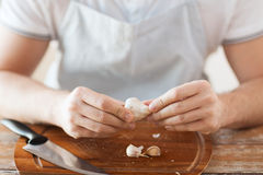 Male hands taking off peel of garlic on board Royalty Free Stock Image