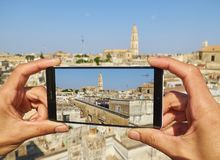 Cattedrale metropolitana di Santa Maria Assunta cathedral of Lecce. Puglia, Italy. Male hands taking a photo with a smartphone of Lecce rooftop view with the Stock Photography