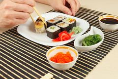 Male hands taking sushi with chopsticks. Assorted sushi, chuka salad, soy sauce and salmon caviar on black bamboo mat. Male hands taking sushi with chopsticks Royalty Free Stock Image