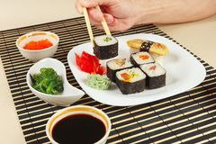 Male hands taking sushi with chopsticks. Sushi set, hiyashi wakame salad, soy sauce and salmon caviar on black bamboo mat. Male hands taking sushi with Royalty Free Stock Photography
