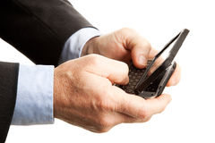 Male Hands Texting. Closeup of a businessman's hands, using his smart phone to text.  Shallow depth of field with focus on the hand and part of the keyboard Stock Photography