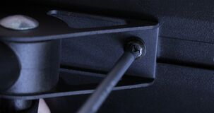 Male hands tighten the screw with a special screwdriver.