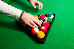 Male hands to place the balls in the triangle to play eight ball Stock Photography