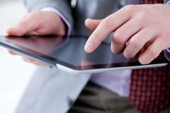 Male hands touching digital tablet. Unrecognizable business man holding a digital tablet Royalty Free Stock Photos
