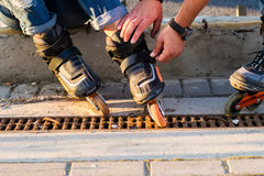 Male hands touching rollerblades. Stock Image
