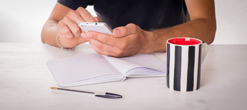 Male hands touching a smartphone. On a table with mug, pen and notebook Royalty Free Stock Image