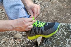 Male hands tying up shoelaces on a running sneaker, close up. Part of sportsman tying sneakers. Leg on a rock. Mens sportswear, Athletes foot, sweatpants, a Stock Images