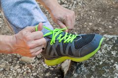 Male hands tying up shoelaces on a running sneaker, close up. Part of sportsman tying sneakers. Leg on a rock. Mens sportswear, Athletes foot, sweatpants, a Stock Photos