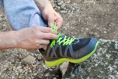 Male hands tying up shoelaces on a running sneaker, close up. Part of sportsman tying sneakers. Leg on a rock. Mens sportswear, Athletes foot, sweatpants, a Royalty Free Stock Photography