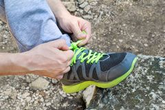 Male hands tying up shoelaces on a running sneaker, close up. Part of sportsman tying sneakers. Leg on a rock. Mens sportswear, Athletes foot, sweatpants, a Royalty Free Stock Images
