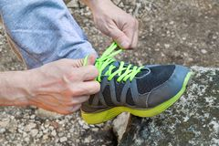 Male hands tying up shoelaces on a running sneaker, close up. Part of sportsman tying sneakers. Leg on a rock. Mens sportswear, Athletes foot, sweatpants, a Royalty Free Stock Photo