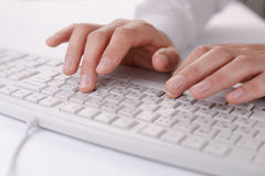 Male hands typing on a computer keyboard. Close up view of male hands typing on a white computer keyboard as he works at his desk in the office royalty free stock photo