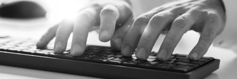 Male hands typing on computer keyboard. Wide view monochrome image of male hands typing on computer keyboard. With lens flare royalty free stock photos