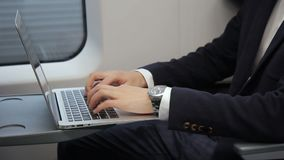 Male hands is typing email on laptop keyboard in the train, close up. The businessman in black suit and with watches on the wrist is sitting and working using stock footage