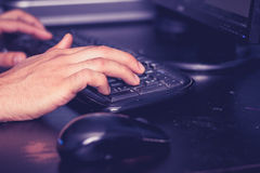 Male hands typing on keyboard at desk Royalty Free Stock Photography