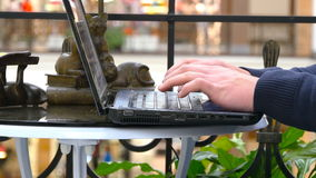 Male hands typing on the keyboard of a laptop in shopping mall.  Stock Photography